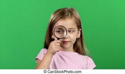 Child is holding a magnifying glass. Green screen