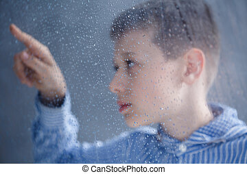 child is looking on water - Autistic child in blue shirt is...