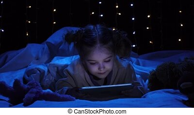 Child is lying on a bed holding a laptop and watching a...