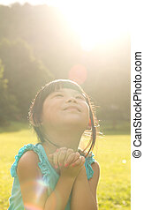 Child is making wish - Asian child is making wish at park...