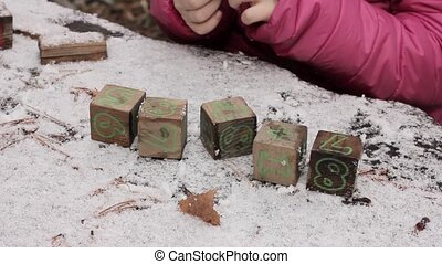 child is played cubes on a snow-covered table, adds up the...