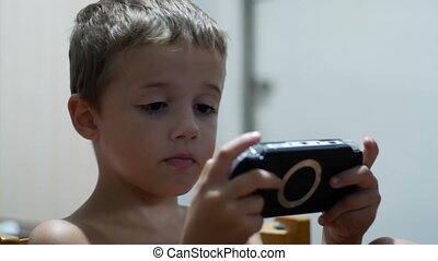 Child is Playing in a Portable Game Console Sitting on a...