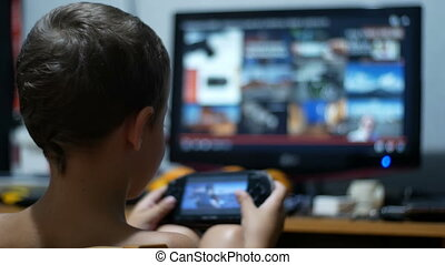 Child is Playing in a Portable Game Console Sitting on a Chair at Home