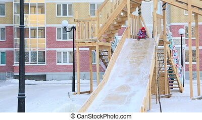 Child is riding slides at playground