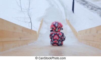 Child is riding slides at playground