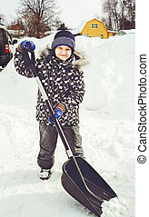 Child is shoveling snow in front of