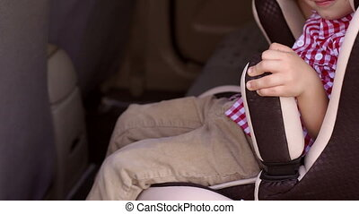 Child is sitting in car seat in car, he holds his hands on the arms of the chair