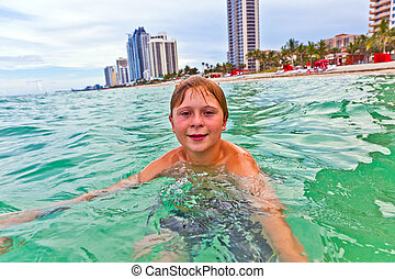 child is swimming in the ocean