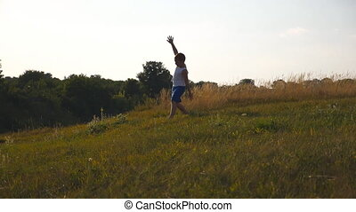 Child jogging at the lawn outdoor. Happy smiling male kid having fun in nature on a summer meadow. Young boy with raised hands running on green grass at the field on sunny day. Slow motion Close up
