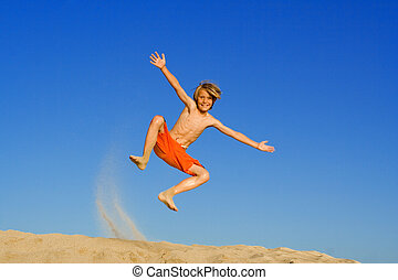 child jumping and playing on beach summer vacation or...