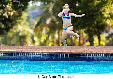 Child jumping in swimming pool. Kids swim.