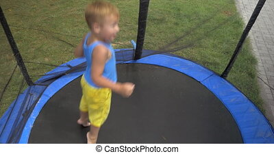 Child jumping inside protected outdoor tramp - Handheld shot...