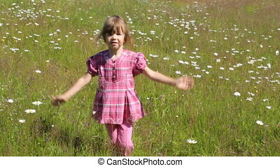 Child jumping on camomile field in summer morning