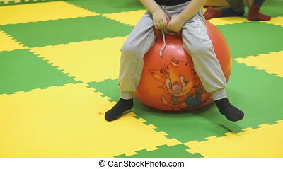 Child jumps on the big red ball