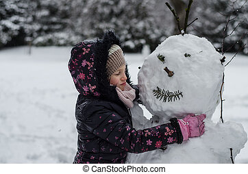 child kand a cold snowman in winter time