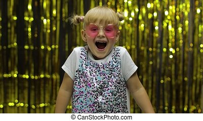 Child kid dancing, celebrating victory, fooling around. Girl posing on background with foil curtain