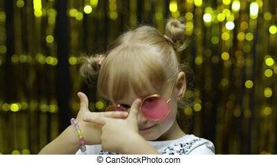 Child kid dancing, waving hands, fooling around. Girl posing on background with foil curtain