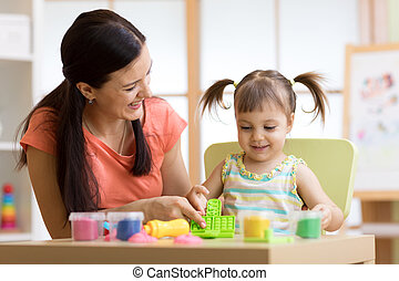 child kid girl and mother play colorful clay toy at nursery or kindergarten