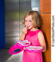child kid girl playing with makeup lipstick in the lift door