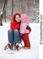 child kiss mother sits in sled in park at winter
