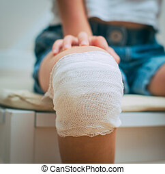 Child knee with adhesive and gauze bandage.