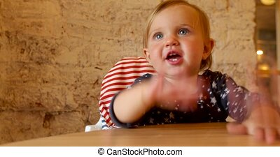 Child knocking on table while waiting for food in cafe -...