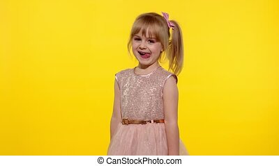 Child laughing, fooling around, showing tongue. Little blonde teen kid girl 5-6 years old posing