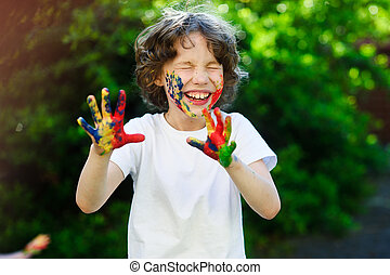 Child laughs, his face and hands in the paint - Child...