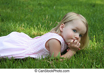 child laying on grass looking with hands on chin