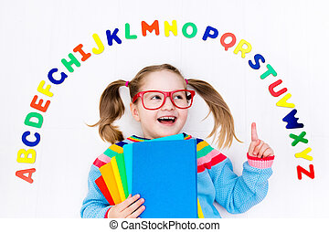Child learning letters of alphabet and reading