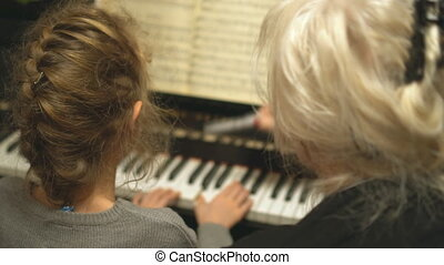 Child learns to play the piano with teacher.