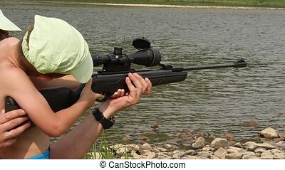 child learns to shoot an air rifle gun with optical sight....