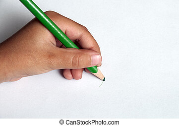 Child left-handed writing with a green pencil