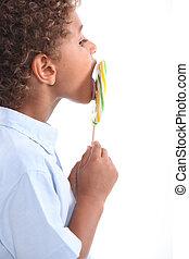 child licking lollipop