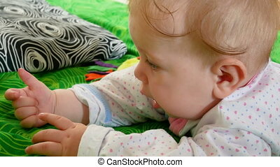 child lies on bed - The little child lies on his belly on...