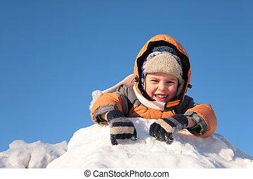 child lies on snow hill
