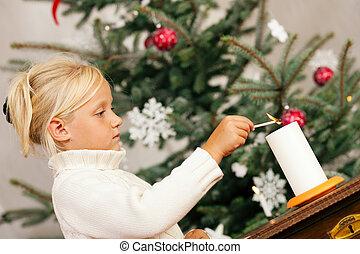 Child lighting Christmas candles