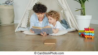 Child listening to fairy-tale while mother reading story at...