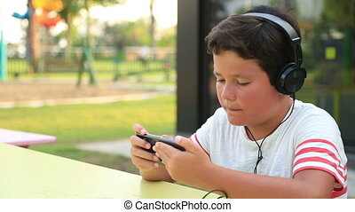Child listening to music and gaming on the smartphone