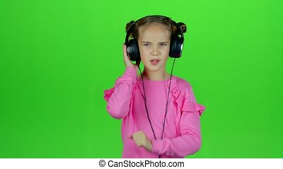 Child listens to the music in the headphones. Green screen....