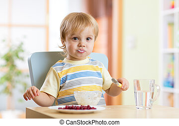 Child little boy eating food with spoon in nursery
