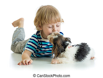 Child little boy kissing puppy dog. Isolated on white background.