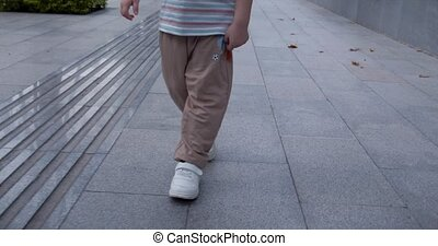 A boy of 4-5 years old is walking, walking down the street, looking at the camera. Concept for kids, family, happy childhood.