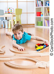 Child little boy playing with wooden railway on the floor