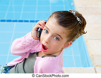 little girl talking mobile phone with surprise