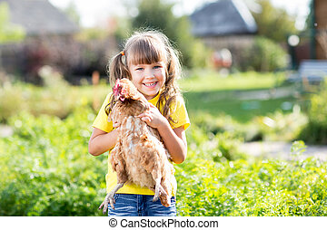 Child little girl with hen outdoor - Child little girl with...