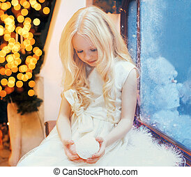 child little girl with snowball toy over christmas tree bokeh at home near window