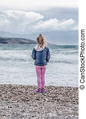 child lookin to the sea