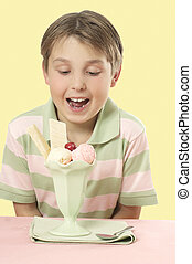 Child looking at an ice cream sundae on a table. - A...