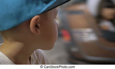 Child looking at bumper cars in amusement park - Close-up ...